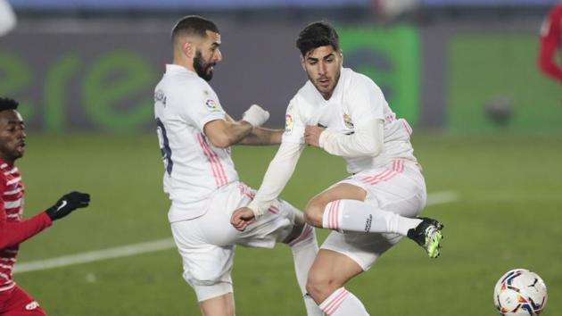 Real Madrid's Karim Benzema, center left, and Real Madrid's Marco Asensio both jump for a shot during the Spanish La Liga soccer match between Real Madrid and Granada at the Alfredo Di Stefano stadium in Madrid, Spain, Wednesday, Dec. 23, 2020.(AP)