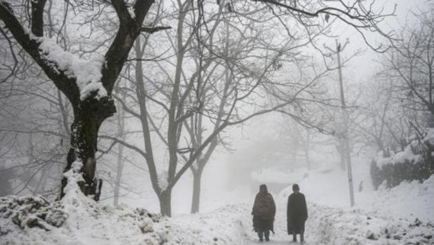 Locals walk on a snow-covered road amid fog at Faqir Gujri on the outskirts of Srinagar.(PTI)