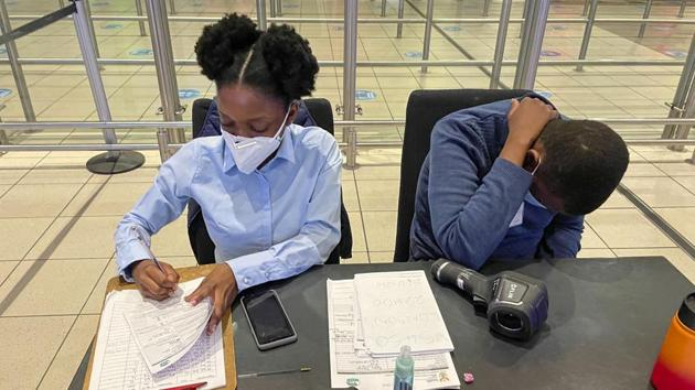 South African health ministry officials collect tracing forms from international travellers at OR Tambo airport on December 21. The check-in was effortless, Delay noted. There is no need to show proof of a Covid-19 test. There are no lines at security, where the big old X-ray machines have been replaced by a high-tech full-body scanner. Just a quick temperature check and turn in a tracking form to a health official. (Jerome Delay / AP)