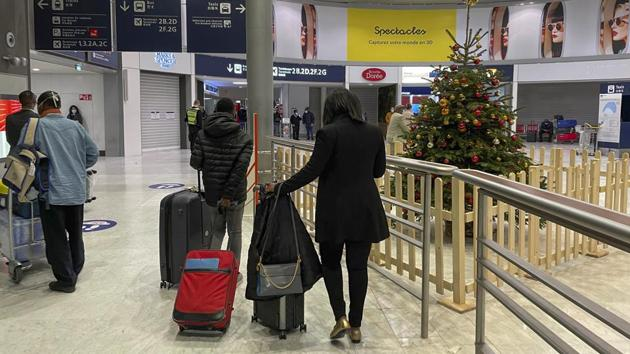 Arriving passengers walk by a Christmas tree at Paris Charles de Gaulle airport on December 22. For those whose final destination was Paris, passengers are triage for immigration, depending on their flight's origin. Proof of a negative Covid-19 test was required here but social distances not necessarily observed. (Jerome Delay / AP)
