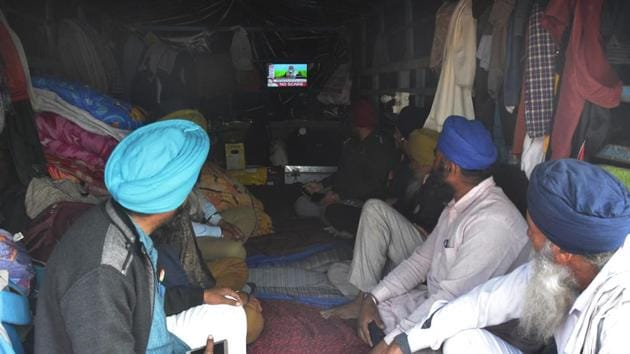 Farmers watching Prime Minster's address on a television screen inside a trolley at Ghazipur border, near Ghaziabad on Friday. (Photo by Sakib Ali /Hindustan Times)