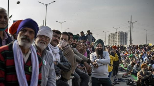Farmers listen to a speaker as they block a major highway in a protest against new farm laws at the Delhi-Uttar Pradesh state border, India, Friday.(AP)