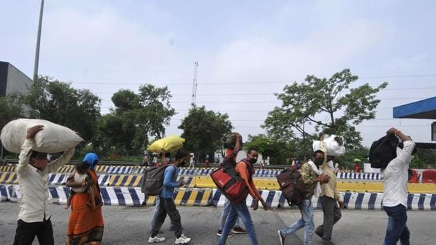 Migrant workers returning from Madhya Pradesh and en route Haryana seen while crossing DND Flyway on foot in Noida.(Sunil Ghosh / Hindustan Times File Photo)