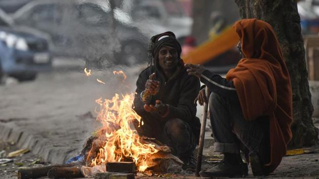 People warm themselves around a bonfire amid cold weather at Nizamuddin in New Delhi.(Biplov Bhuyan/HT PHOTO)
