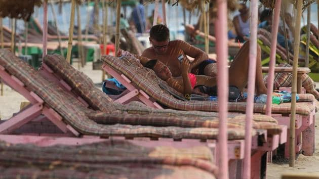 File photo: A foreigner couple spends time at sea side shack as most beds lying empty due to dearth of tourist at Morjim beach in Goa.(Hindustan Times)