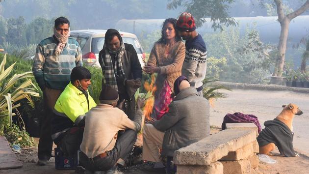 People warm themselves around a bonfire on a cold morning near Yamuna Bank metro station in New Delhi on Sunday.(Raj K Raj/HT Photo)