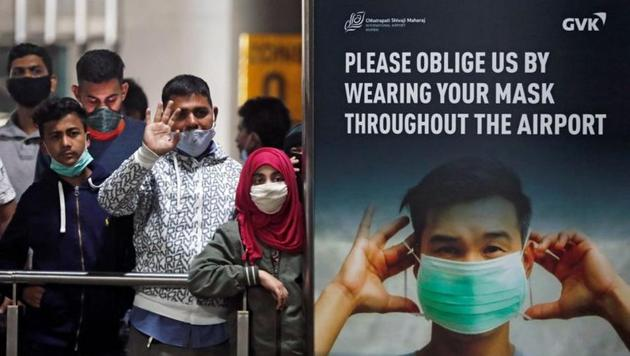 People wearing protective face masks wait for passengers to arrive at Chhatrapati Shivaji Maharaj International Airport after India cancelled all flights from the UK over fears of a new strain of the coronavirus disease (COVID-19), in Mumbai, India,.(REUTERS)