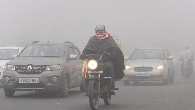 Commuters make their way amid dense fog.(AFP File)