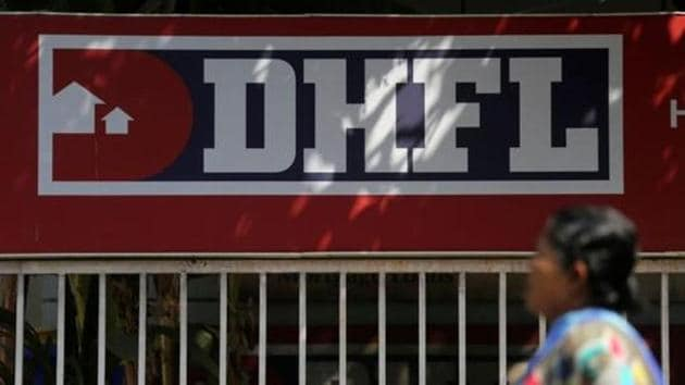 A woman walks past a signboard of Dewan Housing Finance Corporation Ltd. (DHFL) outside its office on the outskirts of Mumbai.(REUTERS)