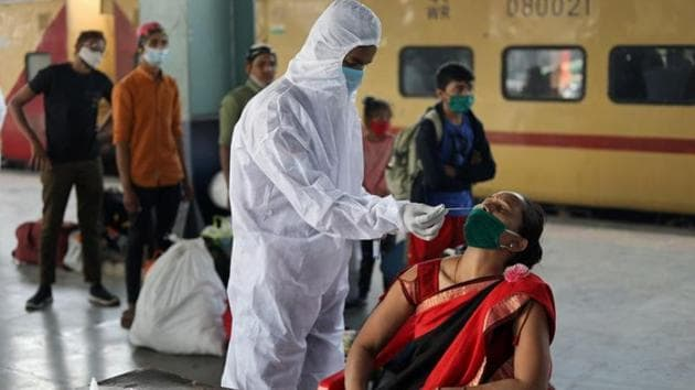 A health worker in personal protective equipment (PPE) collects a swab sample from a woman during a rapid antigen testing campaign for the coronavirus disease (Covid-19), at a railway station platform in Mumbai in this file photo.(Reuters Photo)