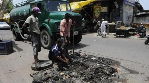 Sanitary workers clear a choked drainage chamber in Nandlalpura area in Indore.(Representative Photo/HT)