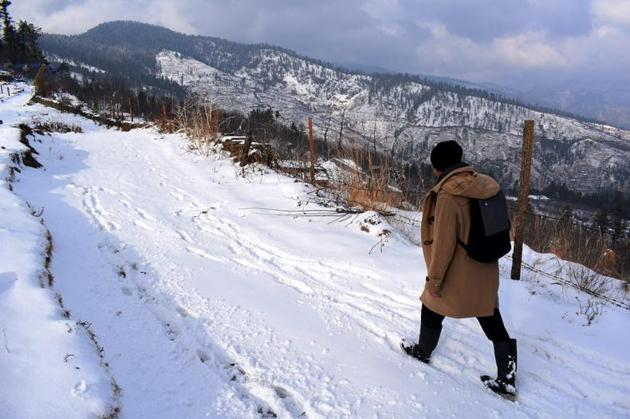 A man walks across a snow-bound stretch at Jarai village in Kotkhai town of Himachal Pradesh. The minimum and maximum temperatures in the hill state have seen a dip since the latest round of snowfall on Tuesday.(Deepak Sansta/HT)