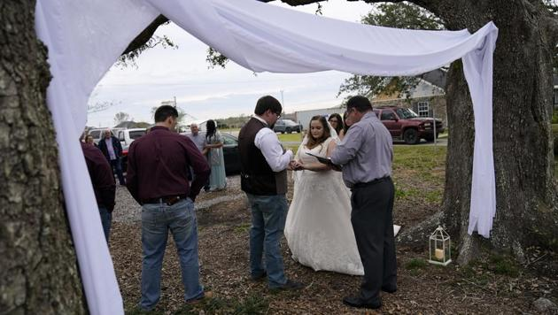 Emily and Taylor Pascale exchange wedding vows outside the home of Taylor's parents, in Grand Lake, La., which was heavily damaged from Hurricanes Laura and Delta.(AP)