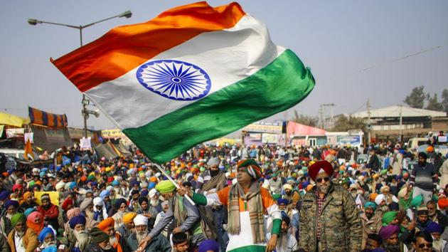 A farmer holds the Tricolor during a protest against the new farm laws, at Singhu Border in New Delhi.(PTI)