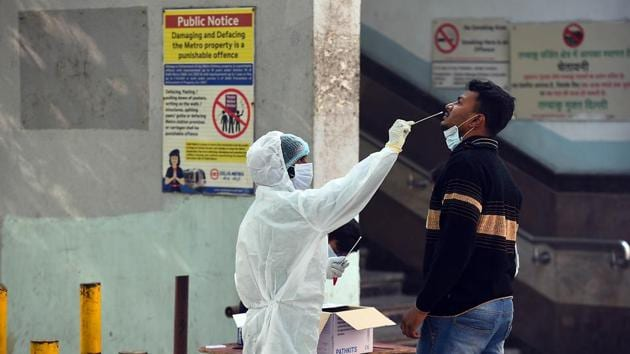 A health worker in PPE collects a swab sample from a person for coronavirus testing, outside New Ashok Nagar Metro station in New Delhi, India.(Raj K Raj/HT PHOTO)
