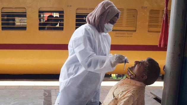 A health worker collects a sample from a train passenger for a Covid test.(ANI)