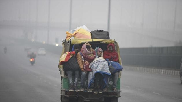 People travelling in a shared vehicle along Delhi-Gurugram Expressway amid foggy conditions and cold weather near IFFCO Chowk, in Gurugram.(Parveen Kumar/Hindustan Times)