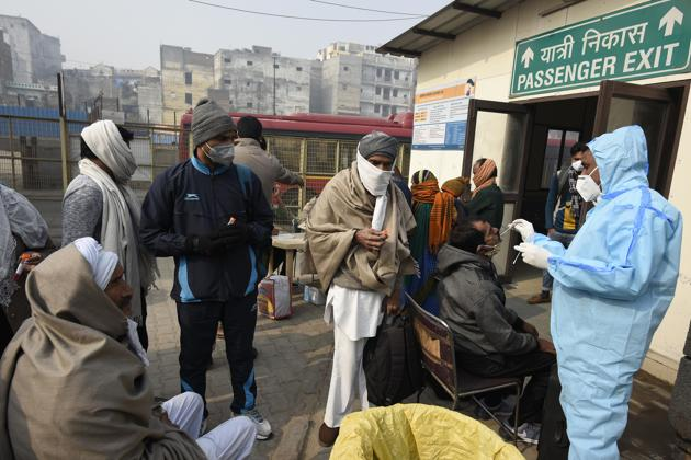 A health worker collects swab samples from passengers for Covid-19 test, New Delhi, January 1, 2020(Biplov Bhuyan/HT PHOTO)