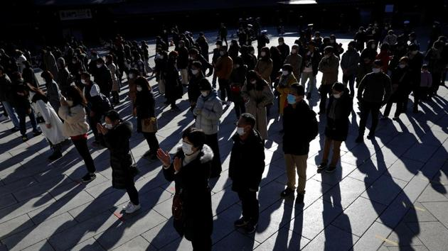 People wearing protective masks amid the Covid-19 outbreak, pray on the first day of the new year at the Meiji Shrine in Tokyo on January 1, 2020.(Reuters Photo)