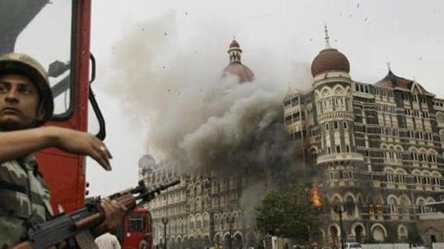 Indian soldier takes cover as the Taj Mahal hotel burns during gun battle between Indian military and militants inside the hotel in Mumbai, India.(AP file photo)