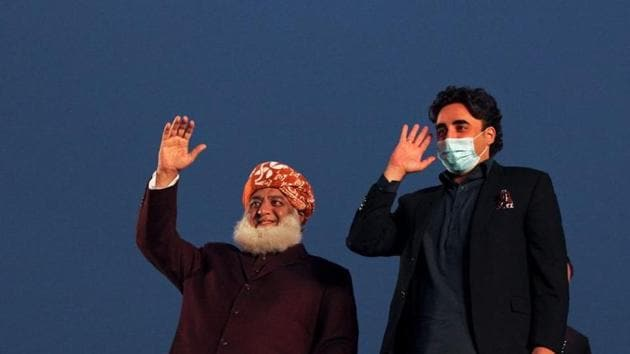 Pakistani politician Maulana Fazlur Rehman and Bilawal Bhutto Zardari, chairman of the Pakistan Peoples Party (PPP), wave to the supporters during an anti-government protest rally organized by the Pakistan Democratic Movement (PDM), an alliance of political opposition parties, in Lahore, Pakistan.(REUTERS)
