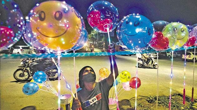 A balloon seller arranges balloons decorated with LED lights at Mutha riverbed road on new year's eve in Pune, India.(Pratham Gokhale/HT Photo)