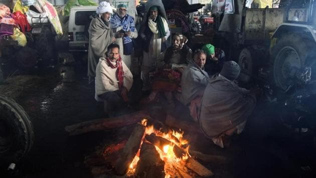 Farmers light fire to beat cold after rain during their ongoing protest against the three farm laws at Gazipur border, in Delhi on Sunday.(ANI File Photo)