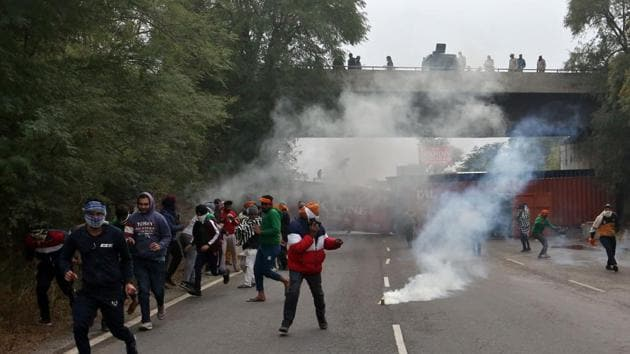 Farmers protesting against newly passed agricultural reforms run away from tear gas fired by police on a national highway at Dharuhera, in the northern state of Haryana, India.(Reuters)
