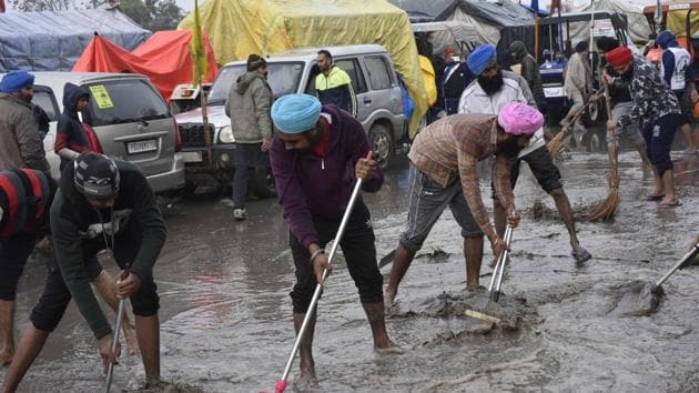 Demonstrators clearing a stretch of rainwater and mud on a rainy day at Singhu border during protests against new farm laws, near New Delhi on Sunday.(Vipin Kumar/HT PHOTO)