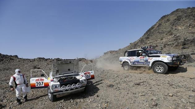 Camporese Fiori's Roberto Camporese and Co-Driver Umberto Fiori parked up as Merinoteam's Alberto Garcia Merino and Co-Driver Julian Jose Garcia Merino drive past during the prologue. (Hamad I Mohammad / REUTERS)