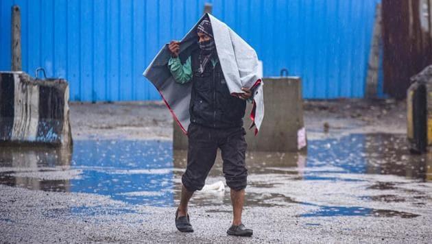 A man covers himself with a plastic sheet during heavy rain near Sarai Kale Khan in New Delhi.(Amal KS/HT PHOTO)