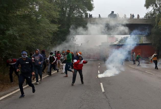 Farmers protesting against newly passed agricultural reforms run away from tear gas fired by police on a national highway at Dharuhera on Sunday.(REUTERS)