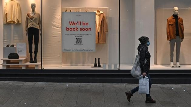 A pedestrian wearing a face mask walks past a shuttered H&M store in Liverpool on January 5. Under new guidelines, expected in place till mid-February, non-essential shops and hospitality will remain closed, while primary and secondary schools would close from January 5 for all pupils except vulnerable children and those whose parents are key workers, Reuters reported. (Paul Ellis / AFP)