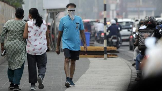 A man has his face covered as a precaution against the coronavirus as he walks on a promenade on the Arabian Sea coast in Mumbai on January 4. The state has seen a decline in active cases in the last four months. It had touched 3,01,752 active cases on September 17. However, a decline in daily cases changed the scenario and consequently active cases also started coming down. (Rajanish Kakade /AP)