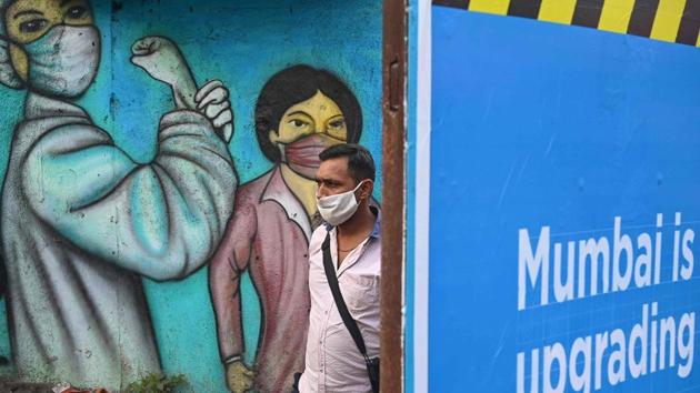 A commuter walks past a wall mural depicting Covid-19 frontline workers in Mumbai on January 5. The ratio of active cases compared to the total cases reported has now dropped to 2.5% against 26.33% recorded on September 17. (Indranil Mukherjee / AFP)