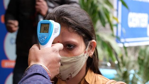 A volunteer wearing a protective mask has her temperature taken during a nationwide trial of a Covid-19 vaccine delivery system in New Delhi on January 2. India on January 5 recorded 16,375 new cases of coronavirus disease (Covid-19), the lowest in more than six months, according to the Union Health Ministry. (T Narayan / Bloomberg)