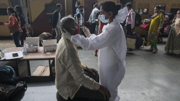 A health worker collects a swab sample from a traveller at Dadar station in Mumbai on January 4. Meanwhile, 20 more people tested positive for the new UK variant of Covid-19 on January 5, the total number of UK returnees having tested positive for the virus variant in India has reached 58. (Pratik Chorge / HT Photo)