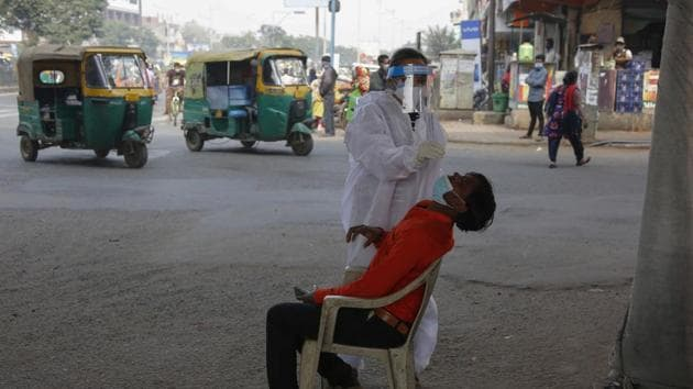 A health worker takes a nasal swab sample of a man to test for Covid-19 in Ahmedabad, India.(AP)