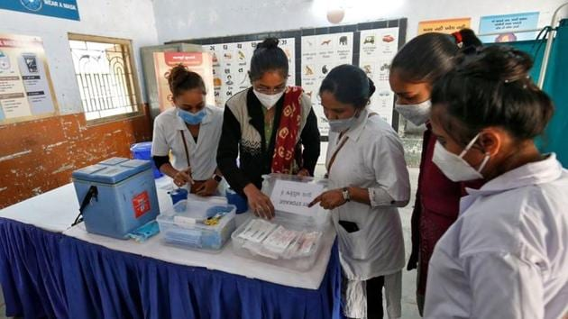 Healthcare workers prepare a vaccination room inside a classroom of a school, which was converted into a temporary Covid-19 vaccination centre in Ahmedabad, on January 4.(Reuters Photo)