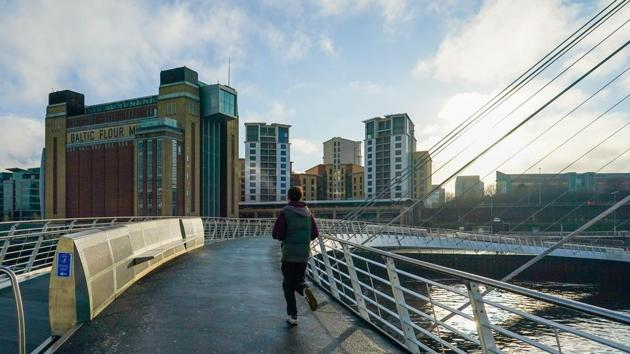 A man runs across the Millennium Bridge in Newcastle on Wednesday as England began a new lockdown to tackle the spread of Covid-19.(Bloomberg)