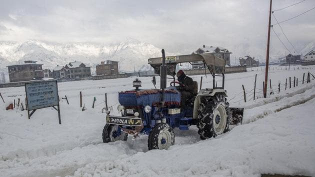 A snow-clearing machine ploughs through a road on the outskirts of Srinagar on Wednesday as Kashmir remained cut off from the rest of the world for the fourth consecutive day due to heavy snowfall .(AP)