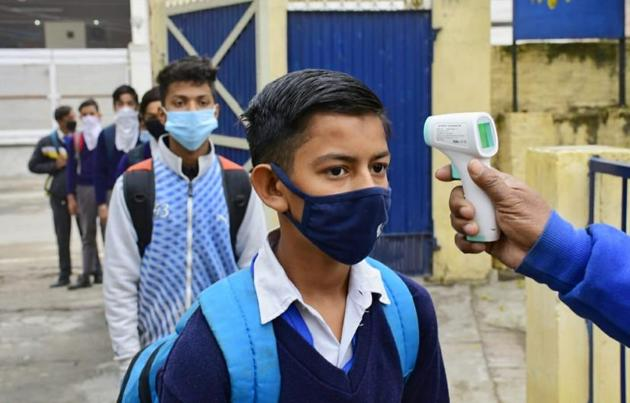 Students of Class 7 of Malwa Khalsa Senior Secondary School, Model Gram, Ludhiana, undergoing thermal screening as they arrive to attend classes on Thursday for the first time since the Covid-19 outbreak in March last year. Teachers ensured social distancing in classrooms.(Harsimar Pal Singh/HT)