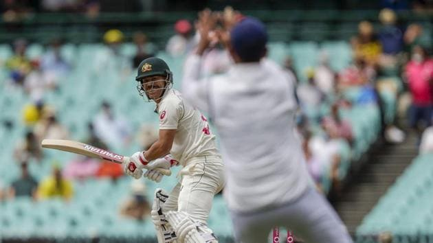 Australia's David Warner, left, watches as he hits the ball to India's Cheteshwar Pujara to be out caught for five runs during play on day one of the third cricket test between India and Australia at the Sydney Cricket Ground, Sydney, Australia, Thursday, Jan. 7, 2021.(AP)
