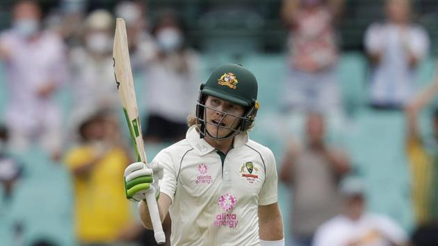 Australia's Will Pucovski waves his bat as he celebrates reaching 50 runs during play on day one of the third cricket test between India and Australia at the Sydney Cricket Ground, Sydney.(AP)
