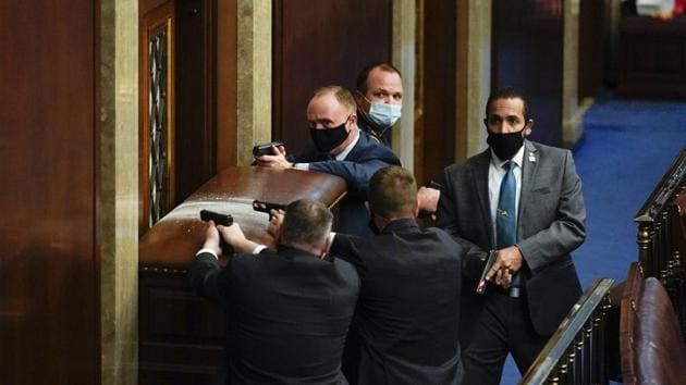 US Capitol Police with guns drawn stand near a barricaded door as protesters try to break into the House Chamber at the US Capitol on January 6 in Washington. (Andrew Harnik / AP)