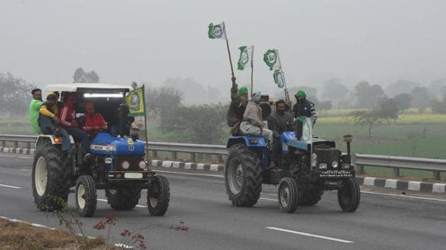 "Farmers waving flags representing a farm union group while riding on tractors during the rally on January 7. The protesting farmers have expressed apprehension that the new laws would pave the way for eliminating the safety of the MSP and do away with the ""mandi"" (wholesale market) system, leaving them at the mercy of big corporates. (Vipin Kumar / HT Photo)"