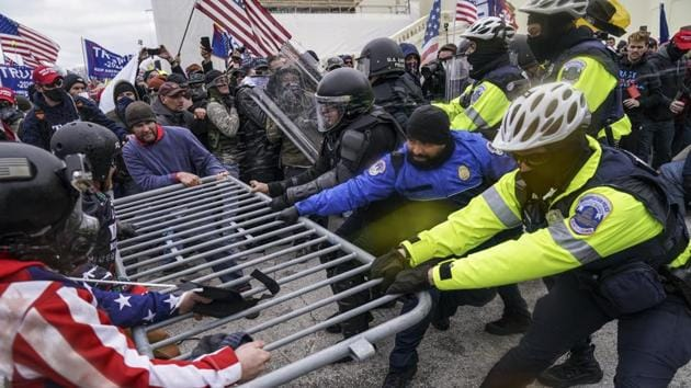 Trump supporters try to break through a police barrier at the Capitol in Washington on January 6. Throngs of maskless demonstrators tore down metal barricades at the bottom of the Capitol's steps while moving to break into the building. (John Minchillo / AP)