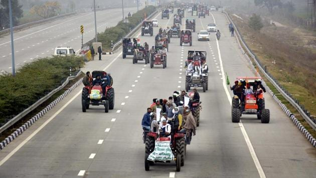 Farmers atop tractors during a rally in protest against new farm laws, in Dasna on January 7. Thousands of farmers protesting on Delhi's borders demanding repeal of three contentious farm laws carries out a tractor march on January 7, converging on the eastern and western peripheral expressways that form a ring around Delhi. (Sakib Ali / HT Photo)