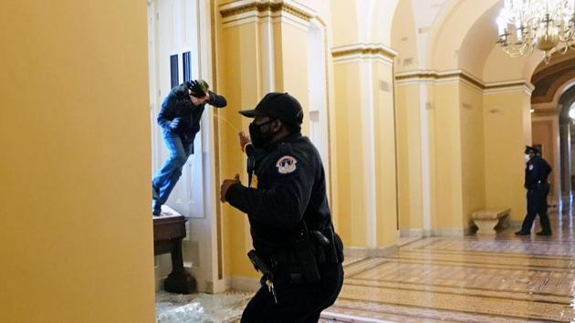 A US Capitol police officer shoots pepper spray at a protestor attempting to enter the Capitol building during a joint session of Congress to certify the 2020 election results on January 6. Reuters reported four deaths in the chaos - one from gunshot wounds and three from medical emergencies. At least 52 people were arrested according to police. (Kevin Dietsch / Pool via REUTERS)