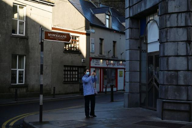 A woman wearing a protective face mask takes a photo of the empty city centre shopping street after the government imposed the highest level of restrictions amid the spread of the coronavirus disease (Covid-19) pandemic, in Galway, Ireland.(Reuters)